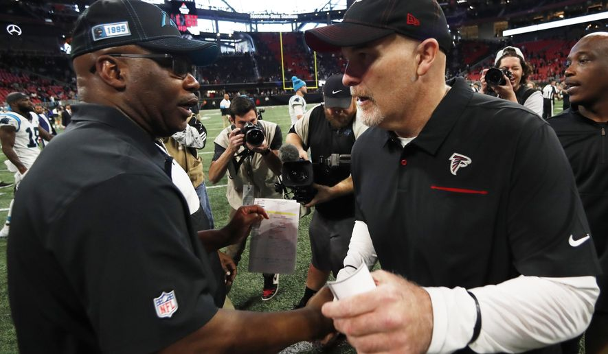 Carolina Panthers interim head coach Perry Fewell, left, speaks with Atlanta Falcons head coach Dan Quinn after an NFL football game, Sunday, Dec. 8, 2019, in Atlanta. The Atlanta Falcons won 40-20. (AP Photo/John Bazemore)