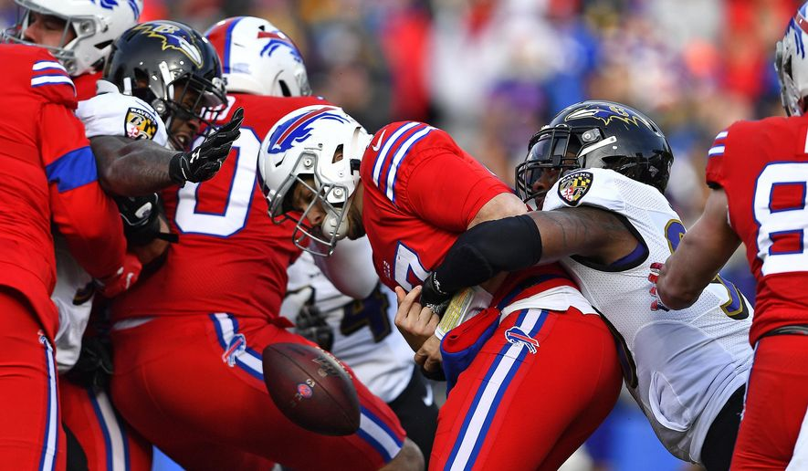 Buffalo Bills quarterback Josh Allen, center, has the ball knocked loose as he is hit by Baltimore Ravens outside linebacker Matt Judon (99), right, during the first half of an NFL football game in Orchard Park, N.Y., Sunday, Dec. 8, 2019. The fumble was recovered by Ravens defensive end Jihad Ward. (AP Photo/Adrian Kraus)