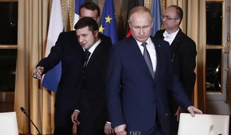 Russian President Vladimir Putin, right, and Ukrainian President Volodymyr Zelensky arrive for a working session at the Elysee Palace Monday, Dec. 9, 2019, in Paris. Russian President Vladimir Putin and Ukraine's president are meeting for the first time at a summit in Paris to find a way to end the five years of fighting in eastern Ukraine. (Ian Langsdon/Pool via AP)