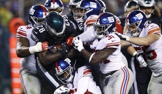 Philadelphia Eagles' Jay Ajayi (28) is tackled by New York Giants' Dalvin Tomlinson (94), Janoris Jenkins (20), Corey Ballentine (25) and Michael Thomas (31) during the first half of an NFL football game against the New York Giants, Monday, Dec. 9, 2019, in Philadelphia. (AP Photo/Matt Rourke)