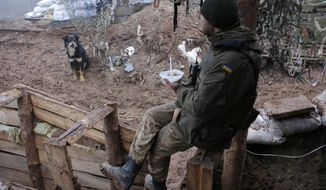 A Ukrainian soldier eats in a trench in the front line near the town of Novoluhanske in the Donetsk region, Ukraine, Monday, Dec. 9, 2019. A long-awaited summit in Paris on Monday aims to find a way to end the war in eastern Ukraine, a conflict that after five years and 14,000 lives lost has emboldened the Kremlin and reshaped European geopolitics. (AP Photo/Vitali Komar)