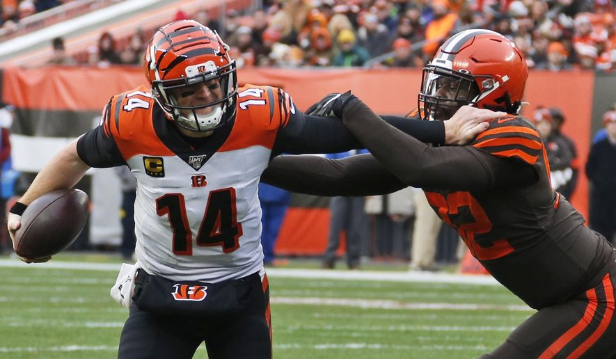 Cincinnati Bengals quarterback Andy Dalton (14) scrambles past Cleveland Browns defensive end Chad Thomas (92) during the second half of an NFL football game, Sunday, Dec. 8, 2019, in Cleveland. (AP Photo/Ron Schwane)