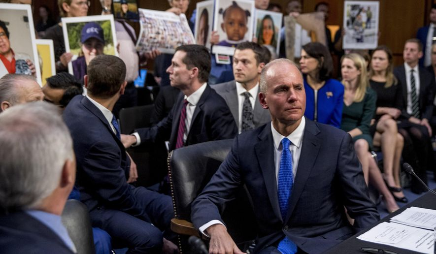 FILE - In this Oct. 29, 2019, file photo Boeing Company President and Chief Executive Officer Dennis Muilenburg, right foreground, watches as family members hold up photographs of those killed in the Ethiopian Airlines Flight 302 and Lion Air Flight 610 crashes during a Senate Committee on Commerce, Science, and Transportation hearing on Capitol Hill. (AP Photo/Andrew Harnik, FIle)