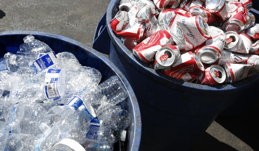 FILE - In this July 5, 2016, file photo, cans and plastic bottles brought in for recycling fill containers at a recycling center in Sacramento, Calif. The state of California is fining CVS Pharmacy a record $3.6 million for failing to redeem deposits on bottles and cans at some of its locations, regulators said Monday, Dec. 9, 2019. (AP Photo/Rich Pedroncelli, File)