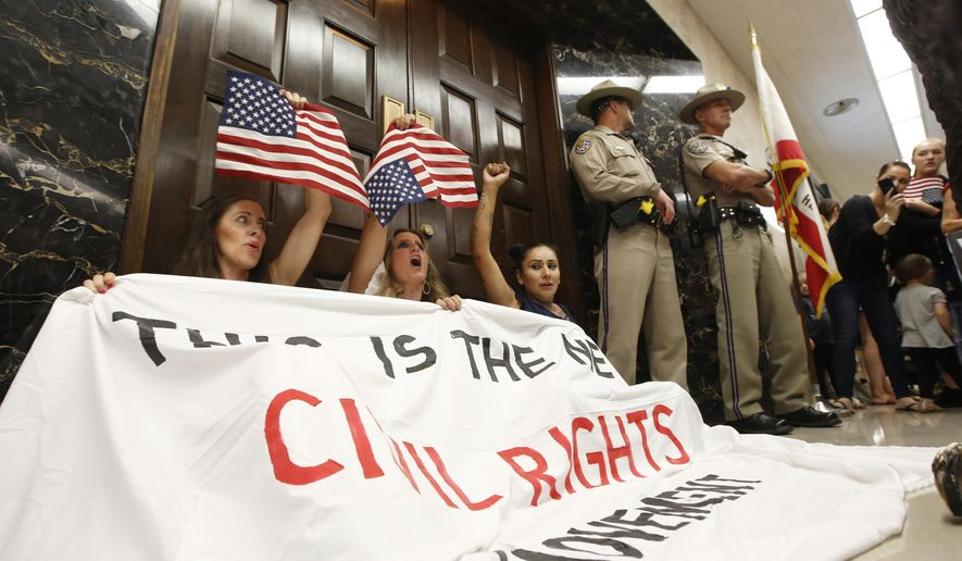 FILE - In this Sept. 4, 2019, file photo Heidi Munoz Gleisner, left, Tara Thornton, center, and Denise Aguilar, right, block the door to Gov. Gavin Newsom's office in protest of the state Legislature's passage of a measure to crack down on doctors who sell fraudulent medical exemptions for vaccinations, at the Capitol in Sacramento, Calif. The three women announced, Monday, Dec. 9, 2019, that they are dropping ballot measures they filed to block the law. (AP Photo/Rich Pedroncelli, File)