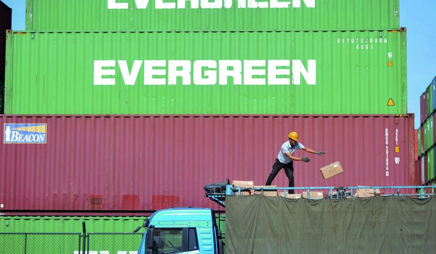 FILE - In this Oct. 14, 2019, file photo, a worker loads imported goods on a truck at a distribution company outside the container port in Qingdao in east China's Shandong province. China's trade with the United States sank again in November as negotiators worked on the first stage of a possible deal to end a tariff war. (Chinatopix via AP, File)