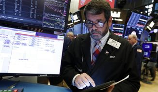 FILE- In this Dec. 5, 2019, file photo trader James MacGilvray works on the floor of the New York Stock Exchange. Stocks are opening mixed on Wall Street on Monday, Dec. 9, as investors weighed the possibility of more U.S. tariffs on China kicking in. (AP Photo/Richard Drew, File)