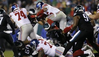 New York Giants' Saquon Barkley (26) leaps over Philadelphia Eagles' Daeshon Hall (74) during the first half of an NFL football game, Monday, Dec. 9, 2019, in Philadelphia. (AP Photo/Michael Perez)