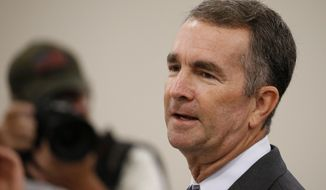 FILE - In this Aug. 20, 2019, file photo, Virginia Gov. Ralph Northam  delivers his budget update before a joint meeting of the House and Senate money committees at the Capitol in Richmond, Va. Virginia is moving toward dropping work requirements for Medicaid enrollees after Democrats won full control of the state legislature for the first time in a generation. (AP Photo/Steve Helber, File)