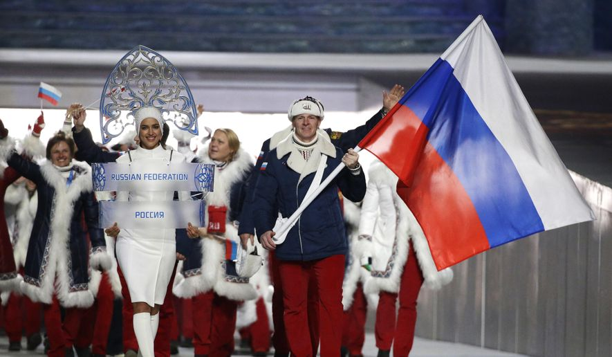 In this Feb. 7, 2014, file photo Alexander Zubkov of Russia carries the national flag as he leads the team during the opening ceremony of the 2014 Winter Olympics in Sochi, Russia. at left is model Irina Shayk carrying the Russian placard. (AP Photo/Mark Humphrey, file)