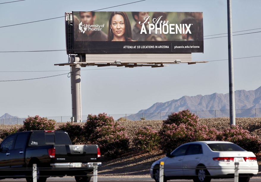 In this Nov 24, 2009, file photo, a University of Phoenix billboard is shown in Chandler, Ariz. The University of Phoenix for-profit college and its parent company will pay $50 million and cancel $141 million in student debt to settle allegations of deceptive advertisement brought by the Federal Trade Commission. (AP Photo/Matt York, File)