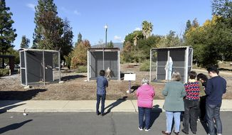 Visitors to a nativity scene displayed outside of Claremont United Methodist Church in Claremont look at baby Jesus, Mary and Joseph as they are displayed in separate cages Monday, Dec. 9, 2019. The church has displayed a controversial nativity scene depicting Mary and Joseph in separate chain link cages with baby Jesus in a separate cage between them.  (Will Lester/The Orange County Register via AP)