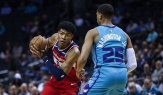 Washington Wizards forward Rui Hachimura, left, looks to drive against Charlotte Hornets forward P.J. Washington in the first half of an NBA basketball game in Charlotte, N.C., Tuesday, Dec. 10, 2019. (AP Photo/Nell Redmond)