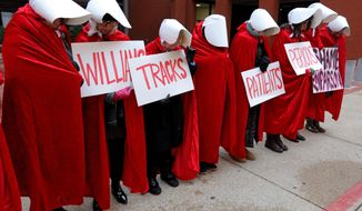 "FILE - In this Oct. 31, 2019, file photo, Planned Parenthood supporters dressed In ""The Handmaid's Tale"" costumes stand in silence in St. Louis before the fourth day of hearings between Planned Parenthood and Missouri Department of Health and Senior Services. Government funding for Missouri Planned Parenthood clinics is at stake in a lawsuit set to be argued before the state Supreme Court on Tuesday, Dec. 10. (Laurie Skrivan/St. Louis Post-Dispatch via AP, File)"