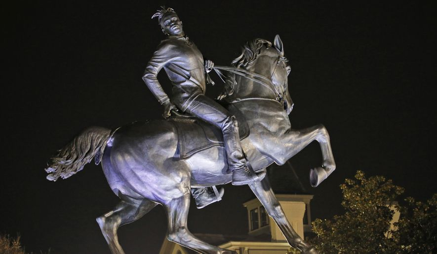 The statue titled Rumor's of War by artist Kehinde Wiley gets fully unveiled after the tarp covering the statue got stuck for a while at the Virginia Museum of Fine Arts in Richmond, Va., Tuesday, Dec. 10, 2019. The monumental bronze sculpture of a young black man astride a galloping horse was unveiled Tuesday, set to be permanently installed in Virginia's capital city, not far from the Confederate monument it mimics. (AP Photo/Steve Helber)