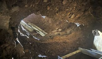This Dec. 9, 2019 photo provided by U.S. Customs and Border Protection (CBP) shows an access point to a tunnel between Nogales, Mexico, and Nogales, Ariz., seen from the U.S. side. The CBP says it busted another cross-border tunnel after arresting a group of four migrants. The agency says agents in Nogales, Ariz., made the discovery on Sunday after a camera operator spotted the migrants. It was just 50 yards (45.7 meters) east of another tunnel that was discovered last week, although that one was incomplete. The Border Patrol says it worked with Mexican authorities to trace the tunnel to Mexico and that it has since destroyed it. (CBP via AP)