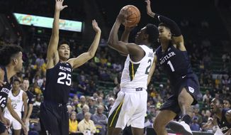 Baylor guard Devonte Bandoo, center, attempts a shot over Butler forward Jordan Tucker, right, and forward Christian David, left, in the first half of an NCAA college basketball game, Tuesday, Dec. 10, 2019, in Waco, Texas. (AP Photo/Rod Aydelotte)