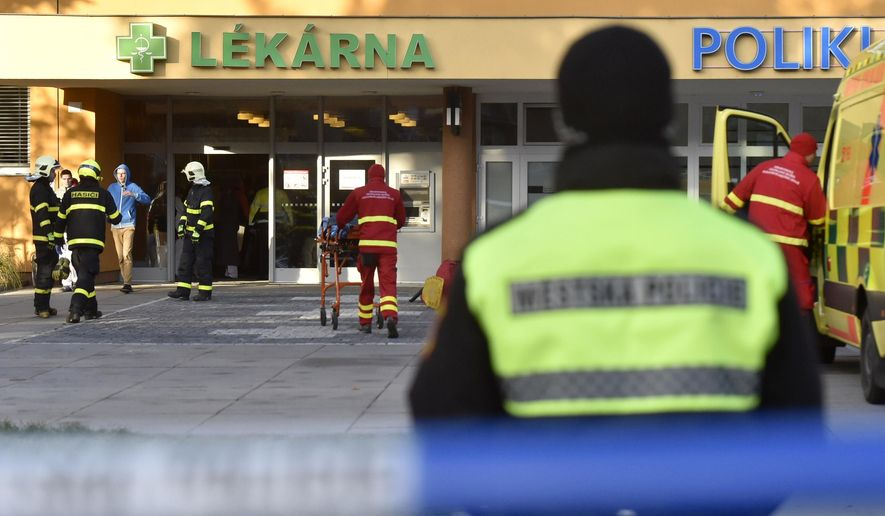 Firefighters, police officers and paramedics in front of the Ostrava Teaching Hospital, after a shooting incident in Ostava, Czech Republic, Tuesday, Dec. 10, 2019. Police and officials say at least four people have been killed in a shooting in a hospital in the eastern Czech Republic. Two others are seriously injured. (Jaroslav Ozana/CTK via AP)
