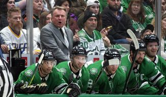 """Dallas Stars interim head coach Rick Bowness yells to his players in the first period of an NHL hockey game against the New Jersey Devils, Tuesday, Dec. 10, 2019, in Dallas. Bowness was announced as interim head coach earlier in the day after former head coach Jim Montgomery was fired for """"unprofessional conduct."""" (AP Photo/Jeffrey McWhorter)"""