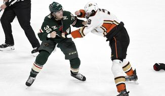 Minnesota Wild's Ryan Hartman, left, and Anaheim Ducks' Derek Grant fight in the first period of an NHL hockey game, Tuesday, Dec. 10, 2019, in St. Paul, Minn. (AP Photo/Tom Olmscheid)