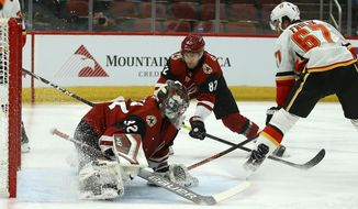 Calgary Flames right wing Michael Frolik (67) gets the puck past Arizona Coyotes goaltender Antti Raanta (32) and Coyotes defenseman Jordan Oesterle (82) for a goal during the first period of an NHL hockey game Tuesday, Dec. 10, 2019 in Glendale, Ariz. (AP Photo/Ross D. Franklin)