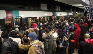 Commuters wait to catch a subway train Tuesday, Dec. 10, 2019 in Paris. Only about a fifth of French trains ran normally Tuesday, frustrating tourists finding empty train stations, and most Paris subways were at a halt. French airport workers, teachers and others joined nationwide strikes Tuesday as unions cranked up pressure on the government to scrap changes to the national retirement system. (AP Photo/Francois Mori)