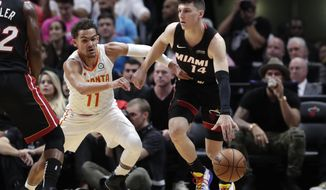 Miami Heat guard Tyler Herro (14) controls the ball as Atlanta Hawks guard Trae Young (11) defends during the first half of an NBA basketball game, Tuesday, Dec. 10, 2019, in Miami. (AP Photo/Lynne Sladky)