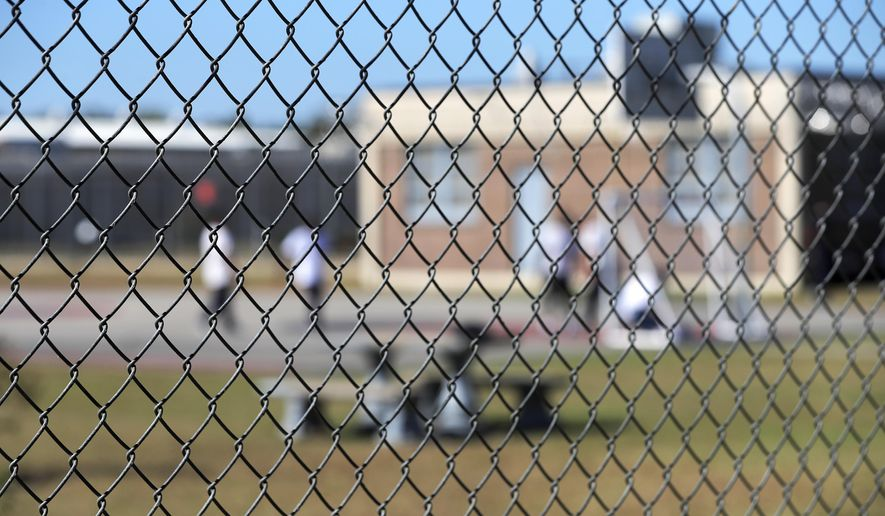 In this Sept. 26, 2019 file photo, detainees sit in a yard during a media tour inside the Winn Correctional Center in Winnfield, La. (AP Photo/Gerald Herbert, File)