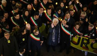 Liliana Segre, an 89-year-old Auschwitz survivor and senator-for-life, center, waves to photographers with Milan's Mayor Giuseppe Sala during an anti-racism demonstration in Milan's Victor Emmanuel II arcade in northern Italy that was joined by mayors of some 600 Italian towns, Tuesday, Dec. 10, 2019. In Italy, controversy flared recently when Segre called for the creation of a parliamentary committee to combat hate, racism and anti-Semitism after revelations that she is subject to some 200 social media attacks each day. (AP Photo/Luca Bruno)