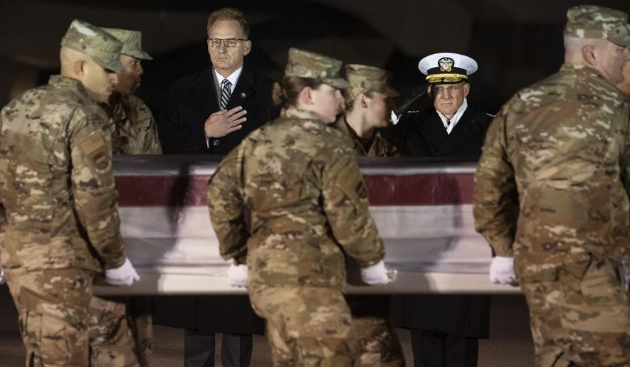 Acting Navy Secretary Thomas Modly, center, and Navy Adm. Michael Gilday, Chief of Naval Operations, look on as an Air Force carry team moves a transfer case containing the remains of Navy Seaman Mohammed Sameh Haitham, of St. Petersburg, Fla., Sunday, Dec. 8, 2019, at Dover Air Force Base, Del. A Saudi gunman killed three people including Haitham in a shooting at Naval Air Station Pensacola in Florida. (AP Photo/Cliff Owen)