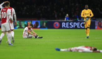 Ajax players react to their elimination from the Champions League after losing the group H soccer match between Ajax and Valencia at the Johan Cruyff ArenA in Amsterdam, Netherlands, Tuesday, Dec. 10, 2019. (AP Photo/Peter Dejong)