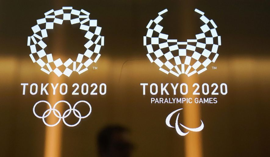 FILE - In this June 11, 2019, file photo, a man walks past the logos of the Tokyo 2020 Paralympics and Olympics in Tokyo. Ticket demand for the Tokyo Paralympics is at record levels. The unprecedented demand follows a similar surge in interest for the Tokyo Olympics. The president of the International Paralympic Committee said Tuesday, Dec. 10, 2019, there were 3.1 million tickets requests in the first lottery phase earlier this year. (AP Photo/Jae C. Hong, File)
