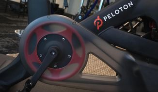 File-This Sept. 26, 2019, file photo shows the Peloton logo on the company's stationary bicycle in New York. Shares of exercise bike company Peloton were under pressure Tuesday, Dec. 10, 2019, from a scathing research report that comes on the heels of blowback from its widely mocked ad. Andrew Left of Citron Research is well known on Wall Street for targeting companies he thinks have flawed business models and placing bets that their stocks will fall. He's now taking aim at New York-based Peloton Interactive Inc. He put a price target of $5 on the stock Tuesday. That would be an 86% drop from where it stood at the close of trading Monday. Peloton went public in September at $29 a share. The stock was down $2.45, or 7%, at $32.32 in afternoon trading Tuesday. (AP Photo/Mark Lennihan, File)