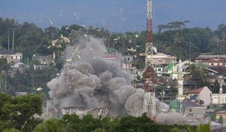 FILE - In this June 9, 2017, file photo, debris flies in the air as Philippine Air Force fighter jets bomb suspected locations of Muslim militants as fighting continues in Marawi city, southern Philippines. Philippine President Rodrigo Duterte decided to end martial law in the southern Philippines after more than two years after government forces weakened Islamic militant groups considerably with the capture and killing of their leaders, his spokesman said Tuesday, Dec. 10, 2019.  (AP Photo/Aaron Favila, File)