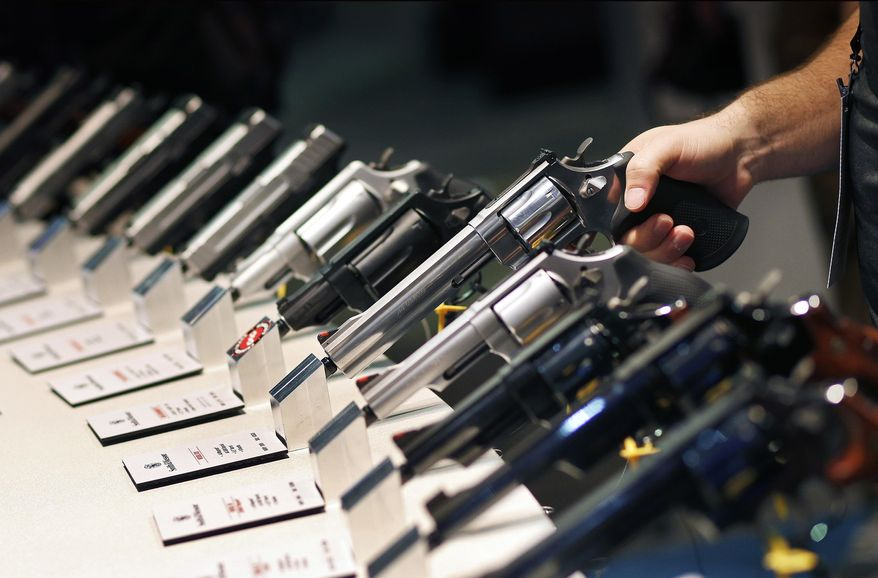 Handguns are displayed at the Shooting, Hunting and Outdoor Trade Show in Las Vegas, Jan. 19, 2016. (AP Photo/John Locher) ** FILE **