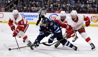 Winnipeg Jets' Blake Wheeler (26) fights for possession of the puck against Detroit Red Wings' Justin Abdelkader (8), Christoffer Ehn (70) and Mike Green (25) during the second period of an NHL hockey game, Tuesday, Dec. 10, 2019, in Winnipeg, Manitoba. (Fred Greenslade/The Canadian Press via AP)