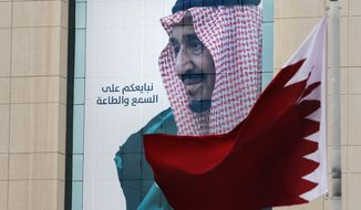 "A Qatari flag flies in front of a banner showing Saudi King Salman with Arabic reads, ""We pledge you to listen and obey"" at a trade center in Riyadh, Saudi Arabia, Monday, Dec. 9, 2019 ahead of the Gulf Cooperation Council ""GCC"", 40th summit. (AP Photo/Amr Nabil)"