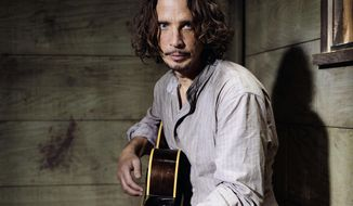 FILE - In this July 29, 2015 file photo, Chris Cornell plays guitar during a portrait session at The Paramount Ranch in Agoura Hills, Calif. The widow of the late Soundgarden frontman is suing the remaining band members and business associates. Vicky Cornell claims they want to withhold royalties from seven of Cornell's solo records. The lawsuit filed Monday, Dec. 9, 2019, in Miami federal court claims that would deprive Vicky Cornell and their two children of hundreds of thousands of dollars in royalties meant for them. (Photo by Casey Curry/Invision/AP, File)