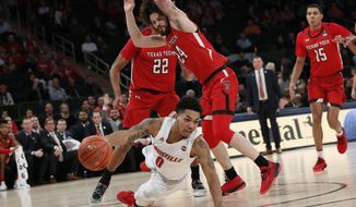 Louisville guard Lamarr Kimble (0) tries to pass after falling with Texas Tech forward TJ Holyfield (22) and Texas Tech guard Avery Benson (24) defending him during the first half of an NCAA college basketball game in the Jimmy V Classic, Tuesday, Dec. 10, 2019, in New York. (AP Photo/Kathy Willens)