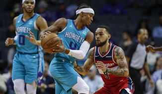 Charlotte Hornets guard Devonte' Graham, left, looks for room to drive against Washington Wizards guard Chris Chiozza in the first half of an NBA basketball game in Charlotte, N.C., Tuesday, Dec. 10, 2019. (AP Photo/Nell Redmond)