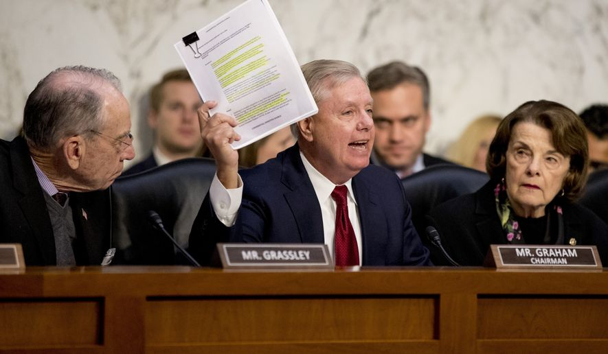 Chairman Lindsey Graham, R-S.C., center, accompanied by Sen. Chuck Grassley, R-Iowa, left, and Ranking Member Sen. Dianne Feinstein, D-Calif., right, holds up a report while giving an opening statement as Department of Justice Inspector General Michael Horowitz, center foreground, testifies at a Senate Judiciary Committee hearing on the Inspector General's report on alleged abuses of the Foreign Intelligence Surveillance Act, Wednesday, Dec. 11, 2019, on Capitol Hill in Washington. (AP Photo/Andrew Harnik)