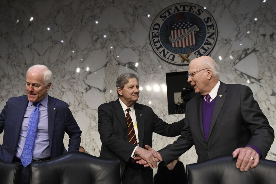 Sen. John Kennedy, R-La., center, shakes hands with Sen. Patrick Leahy, D-Vt., right, as Sen. John Cornyn, R-Texas, left, sits down before the start of a Senate Judiciary Committee hearing on Capitol Hill in Washington, Wednesday, Dec. 11, 2019, to look at the Inspector General's report on alleged abuses of the Foreign Intelligence Surveillance Act. (AP Photo/Susan Walsh)