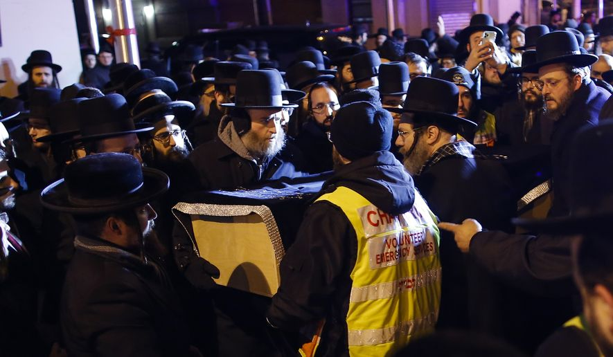 Orthodox Jewish men carry the casket of Mindel Ferencz who was killed in a kosher market that was the site of a gun battle in Jersey City, N.J., Wednesday, Dec. 11, 2019. Ferencz, 31, and her husband owned the grocery store. The Ferencz family had moved to Jersey City from Brooklyn. (AP Photo/Eduardo Munoz Alvarez)