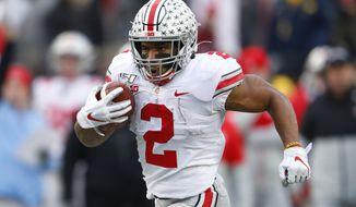 FILE - In this Nov. 30, 2019, file photo, Ohio State running back J.K. Dobbins runs for a 33-yard touchdown against Michigan in the second half of an NCAA college football game, in Ann Arbor, Mich. Dobbins was selected to The Associated Press All-Big Ten Conference team, Wednesday, Dec. 11, 2019. (AP Photo/Paul Sancya, File)