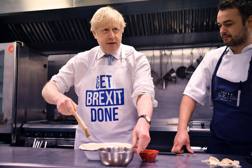 Britain's Prime Minister Boris Johnson prepares a pie at the Red Olive catering company while on the campaign trail, in Derby, England, Wednesday, Dec. 11, 2019 Britain goes to the polls on Dec. 12. (Ben Stansall/Pool Photo via AP)