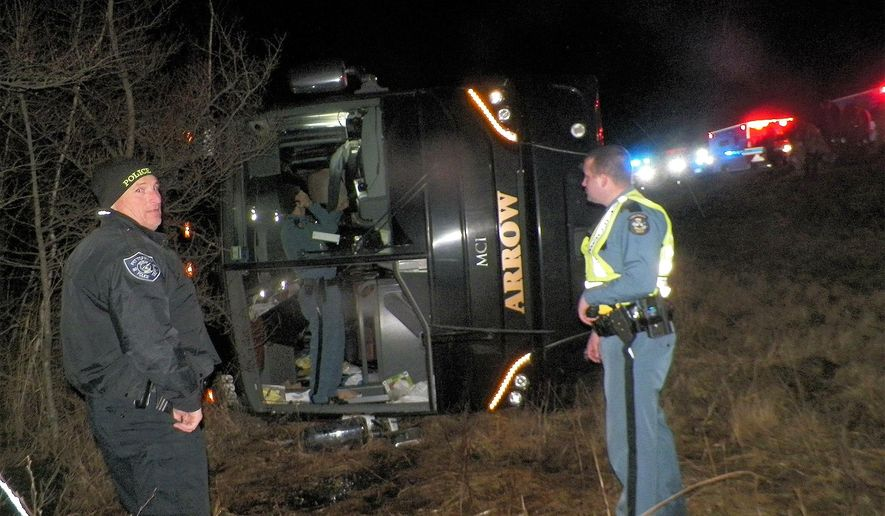 Maine state police investigate the scene, Wednesday, Dec. 11, 2019, in Burnham, Maine, where a charter bus from New York with dozens of people on board overturned on Interstate 95 after the driver fell asleep, according to authorities. Multiple passengers suffered minor injuries, Maine State Police said. (Maine State Police via AP)