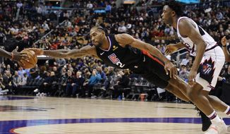 Los Angeles Clippers forward Kawhi Leonard (2) stretches for the ball as Toronto Raptors forward OG Anunoby (3) looks on during the second half of an NBA basketball game, Wednesday, Dec. 11, 2019, in Toronto. (Nathan Denette/The Canadian Press via AP)