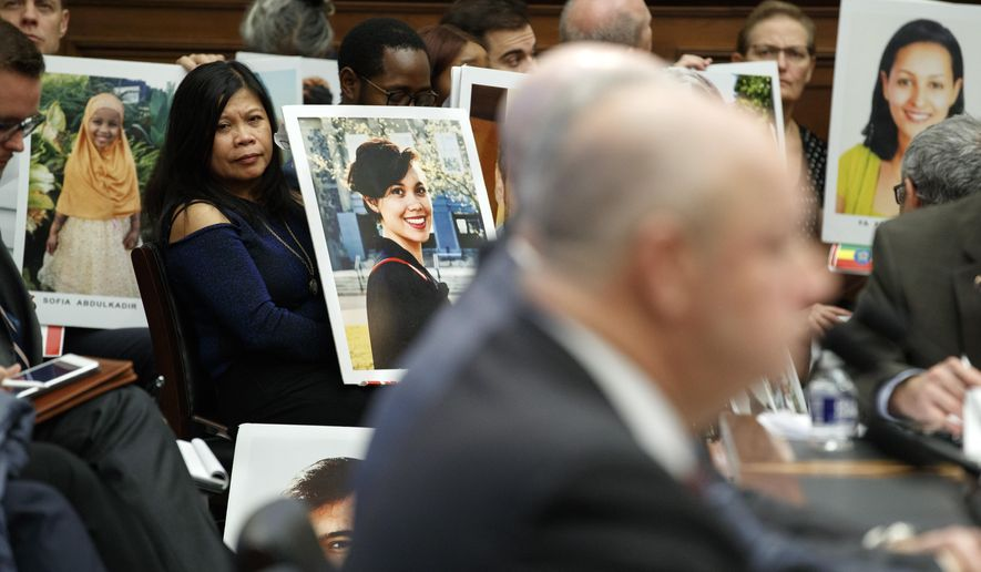 Family members of people who died in crashes of the Boeing 737 MAX hold photographs of their lost loved ones as FAA Administrator Stephen Dickson testifies during a House Transportation Committee hearing on the Boeing 737 MAX, Wednesday, Dec. 11, 2019, on Capitol Hill in Washington. (AP Photo/Jacquelyn Martin)