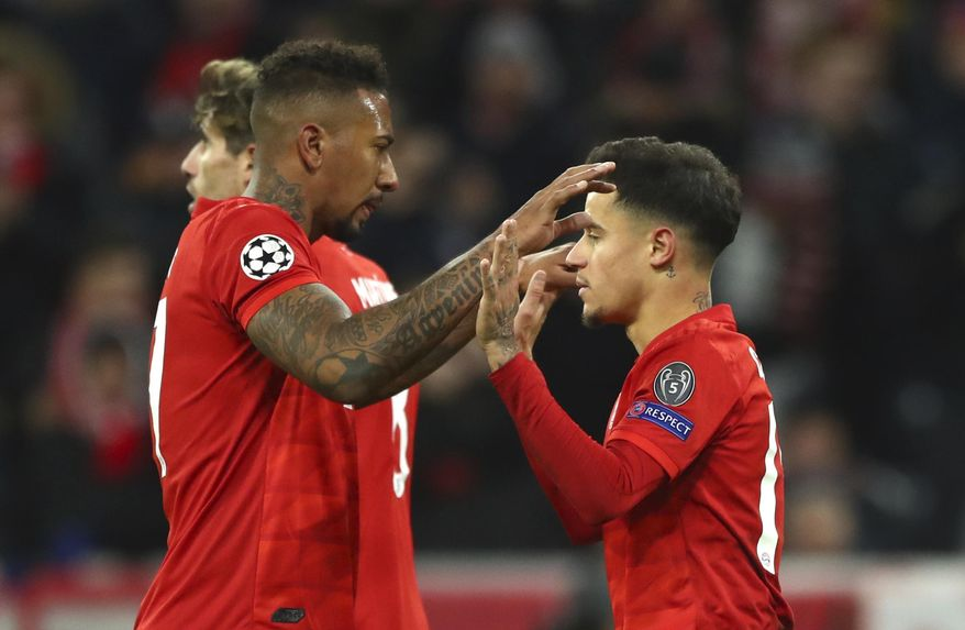 Bayern's Philippe Coutinho, right, celebrates with Bayern's Jerome Boateng after scoring his sides third goal during the Champions League group B soccer match between Bayern Munich and Tottenham Hotspur at the Allianz Arena stadium, in Munich, Wednesday, Dec. 11, 2019. (AP Photo/Matthias Schrader)