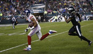 New York Giants' Darius Slayton, left, runs past Philadelphia Eagles' Ronald Darby to score a touchdown during the first half of an NFL football game, Monday, Dec. 9, 2019, in Philadelphia. (AP Photo/Michael Perez)